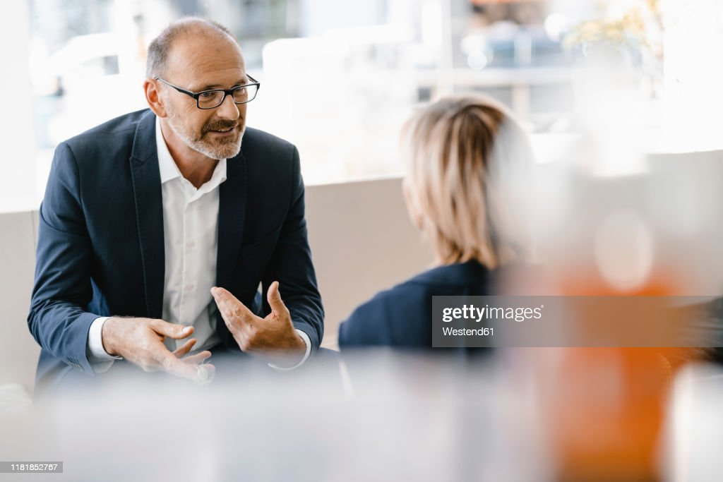 Businessman and woman having a meeting in a coffee shop, discussing work : Stock-Foto