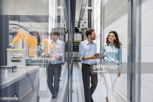businessman and woman having a meeting in high tech company - produktionsgerät stock-fotos und bilder