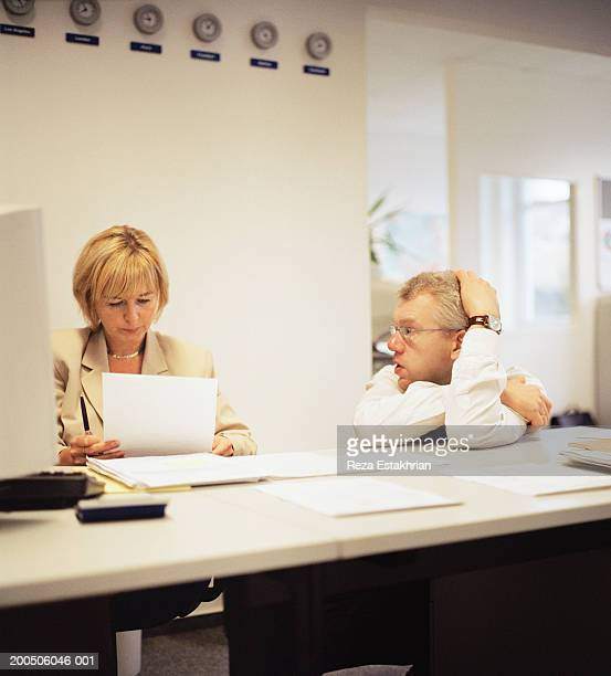 Businessman and woman having discussion at desk