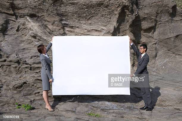 Businessman and woman holding white message board.