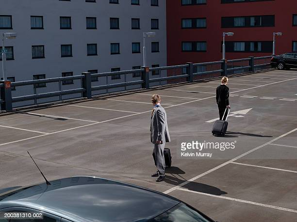 Businessman and woman in car park, heading in different directions
