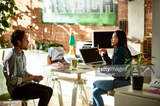 businessman and woman in modern office talking - job interview stock pictures, royalty-free photos & images
