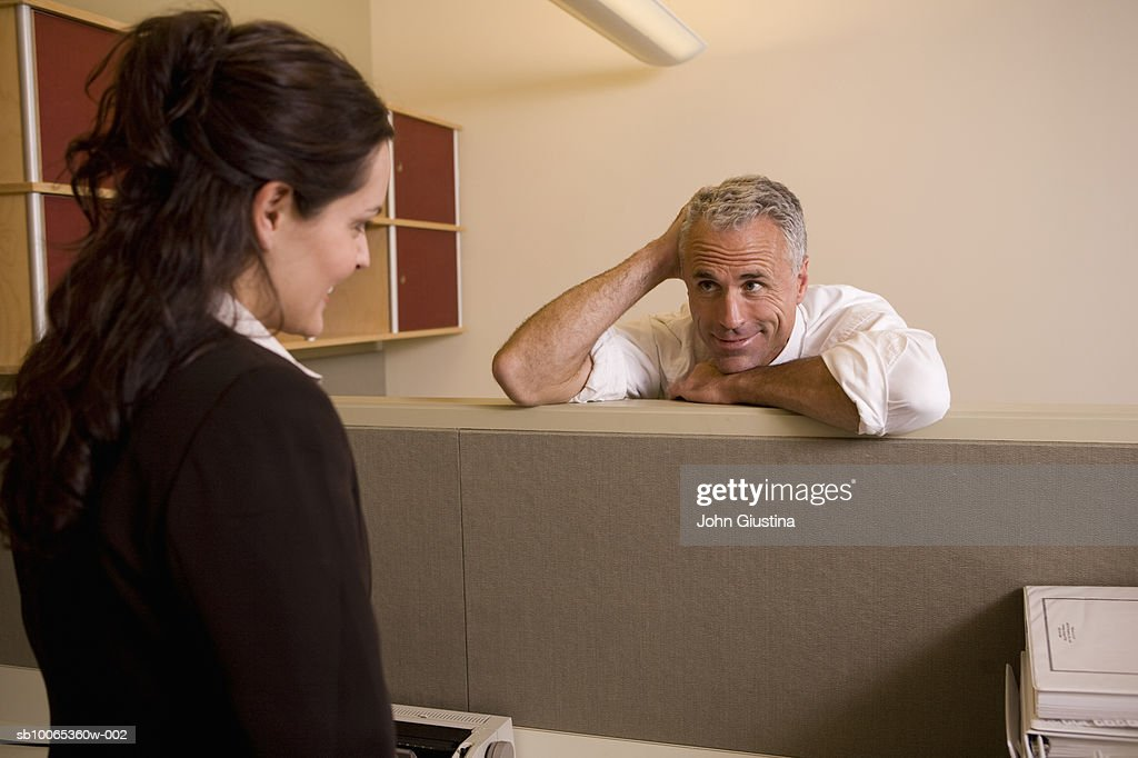 Businessman and woman in office looking at each other, smiling : Foto stock