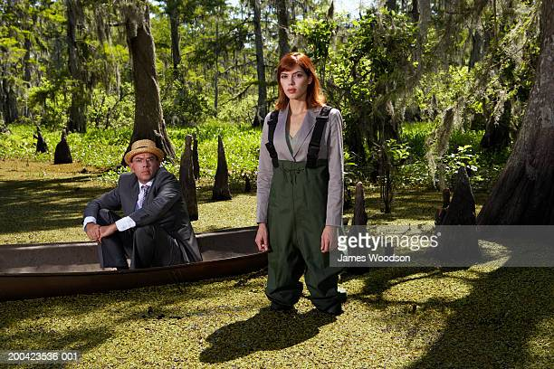 Businessman and woman in swamp, man in canoe, portrait