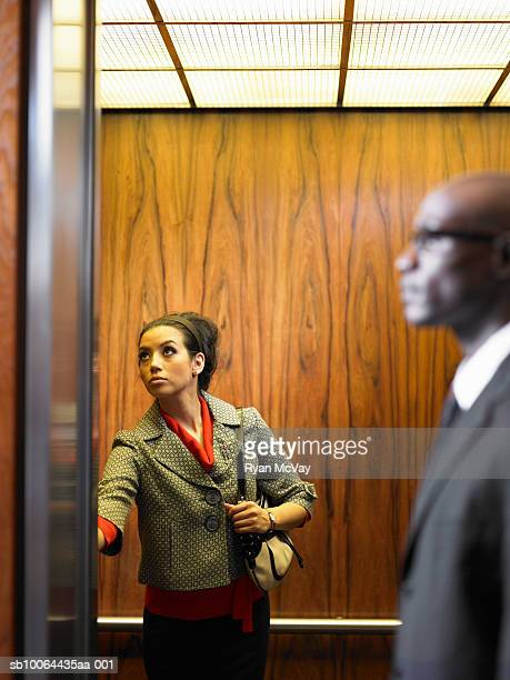 businessman and woman inside elevator, woman pushing button - impatient stock pictures, royalty-free photos & images