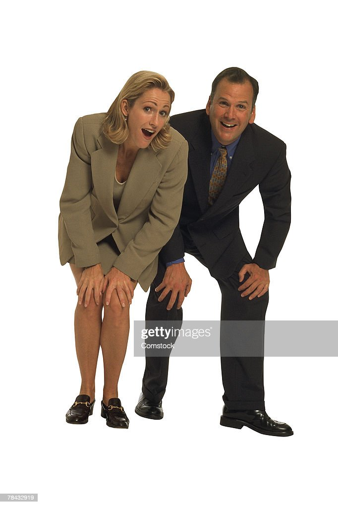 Businessman and woman leaning forward with hands on knees : Stockfoto