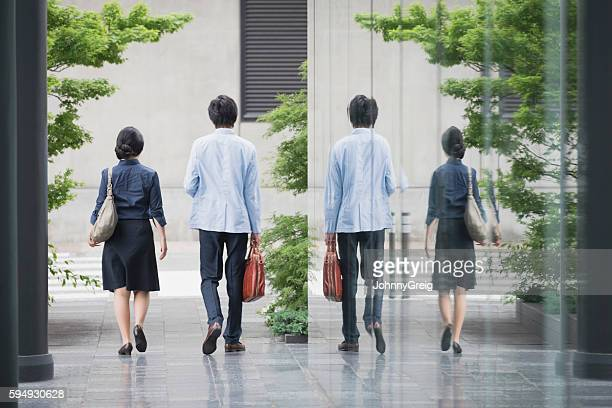 Businessman and woman leaving work with reflection in glass