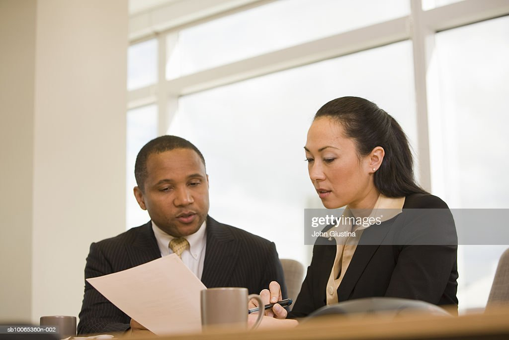 Businessman and woman looking at document in conference room : Foto stock