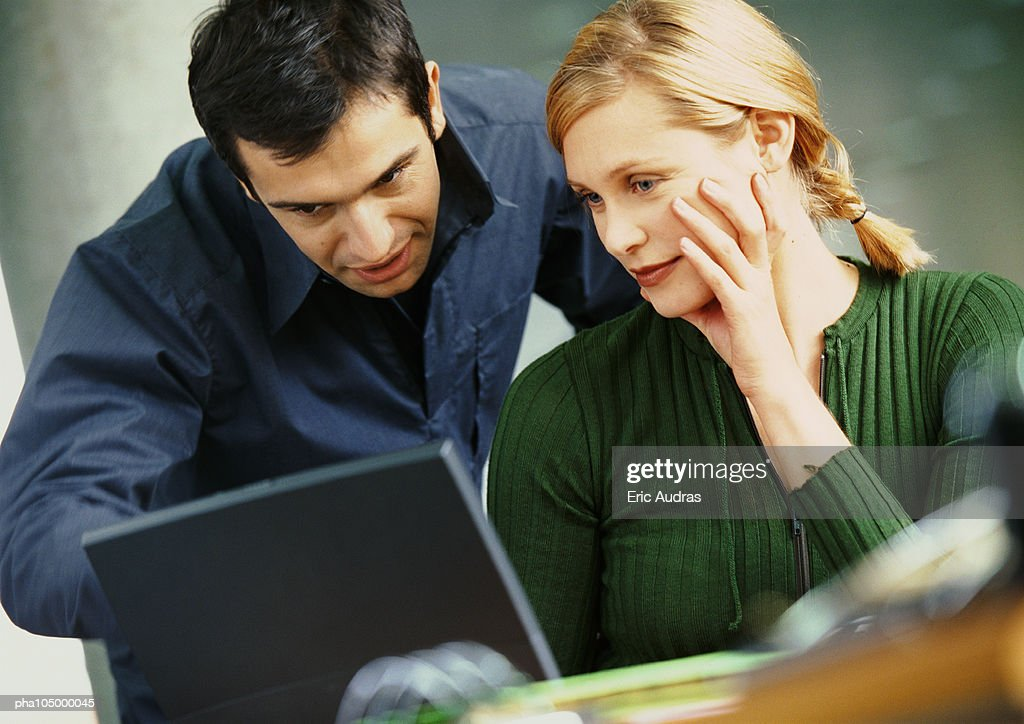 Businessman and woman looking at laptop computer : Stockfoto