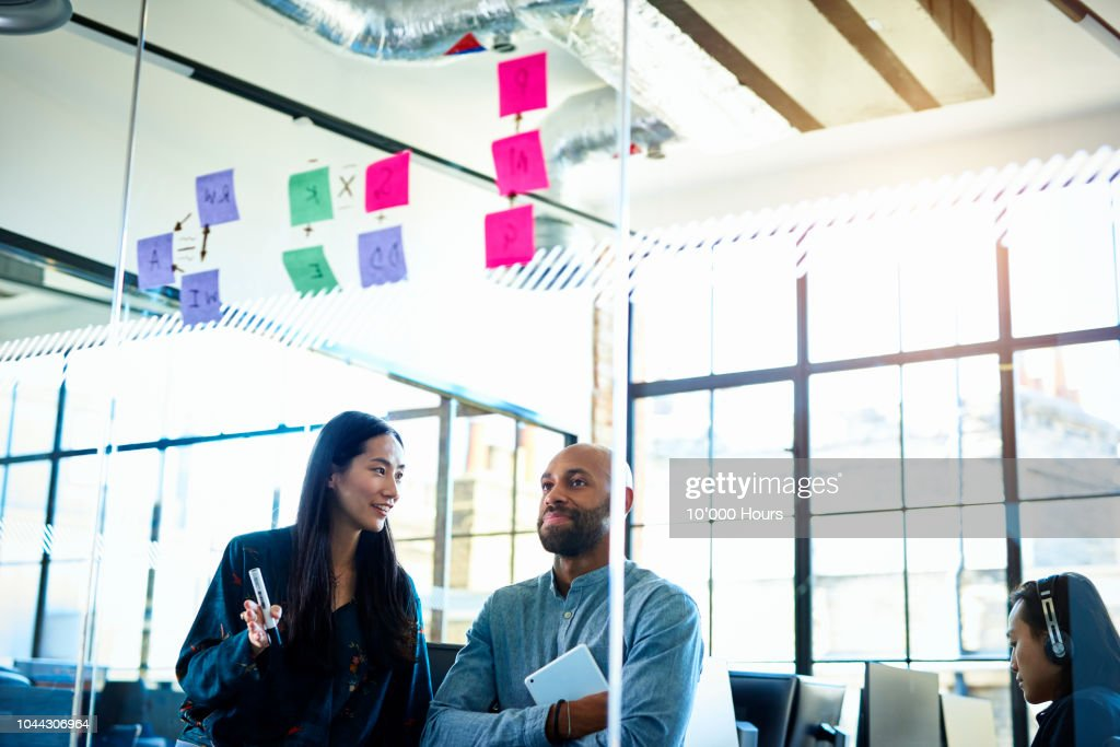 Businessman and woman looking at sticky notes on glass : ストックフォト