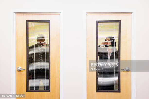 Businessman and woman peeking through blinds on doors