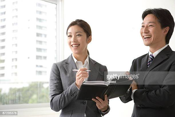 Businessman and woman planning with diary, smiling