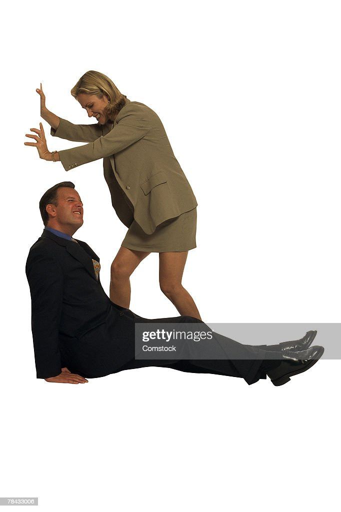 Businessman and woman pushing against unseen object : Stockfoto
