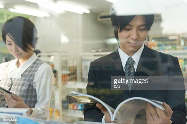 Businessman and woman reading magazine