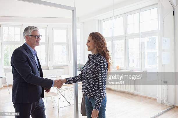 Businessman and woman shaking hands in bright office
