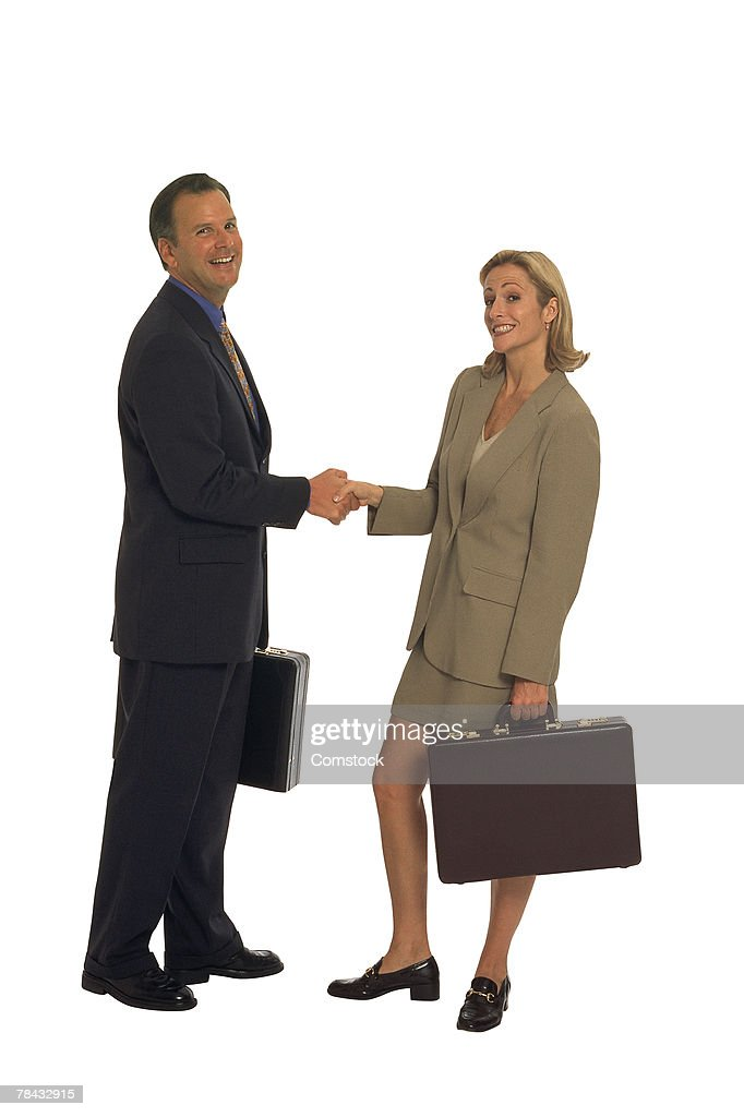 Businessman and woman shaking hands : Stockfoto