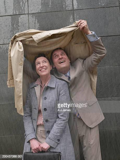 Geschäftsmann und -frau Zuflucht unter Mann's coat im Regen und smili