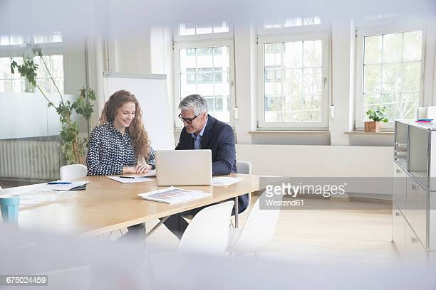Businessman and woman sitting at boardroom table looking at documents