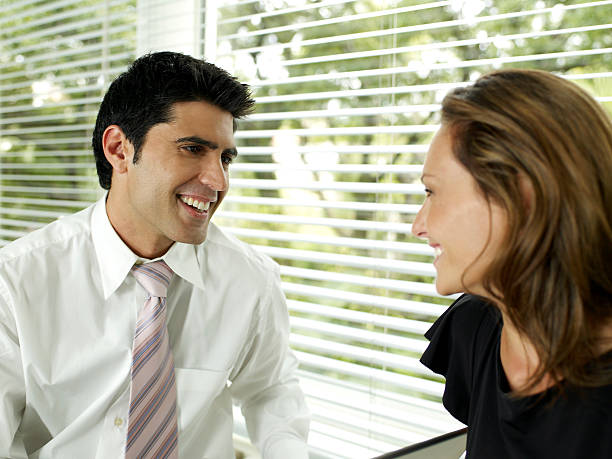 Businessman and woman sitting by blinds looking at each other, smiling