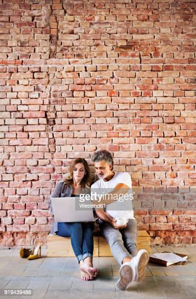 businessman and woman sitting in a loft, using laptop, founding a start-up company - founder stock pictures, royalty-free photos & images