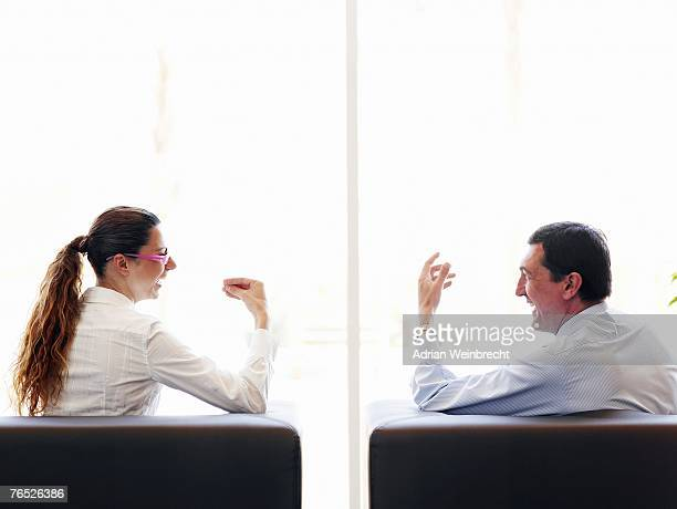 Businessman and woman sitting in armchairs, talking, rear view