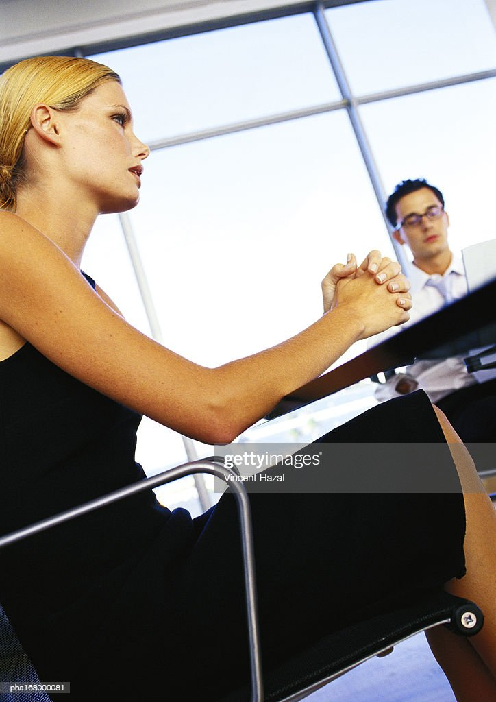 Businessman and woman sitting in office, side view : Stockfoto