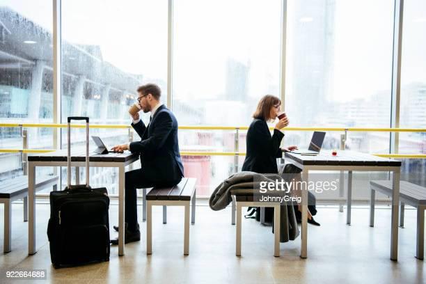 ビジネスマンおよびラップトップに戻るを使用して駅に座っている女性 - 背中合わせ ストックフォトと画像