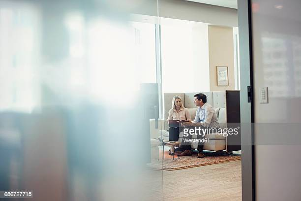 businessman and woman sitting on sofa using digital tablets - private stock photos and pictures