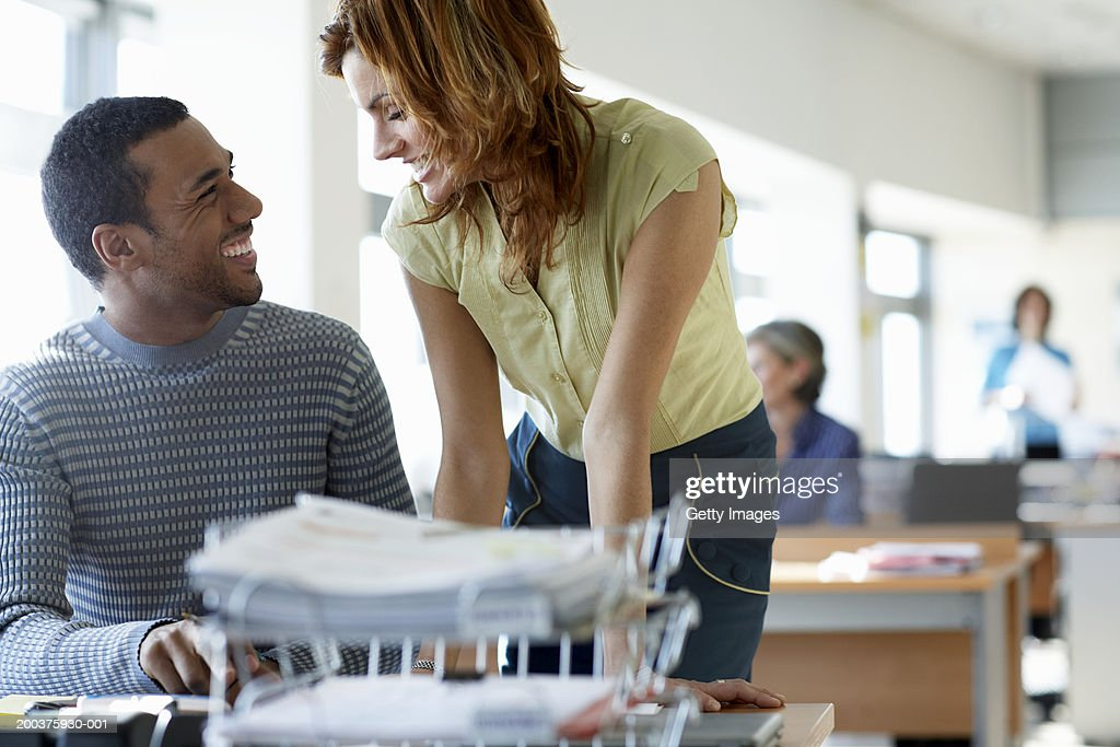 Businessman and woman smiling at each other in office : Stock Photo