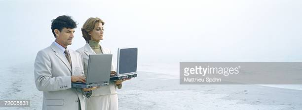 businessman and woman standing, holding laptops on beach - hot desking stock pictures, royalty-free photos & images