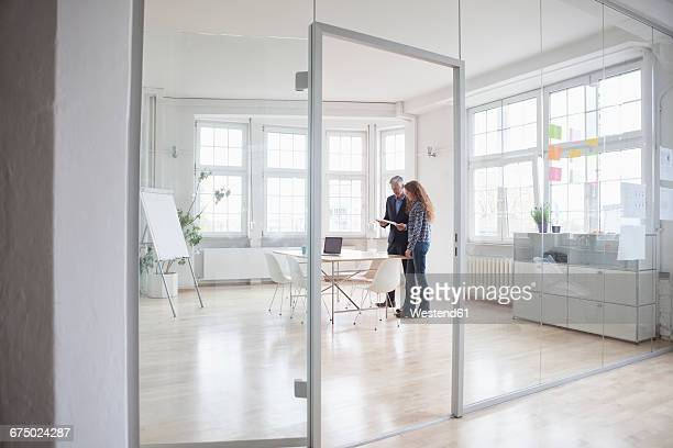 Businessman and woman standing in bright office
