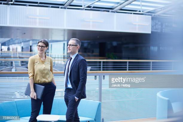 Businessman and woman standing in office atrium