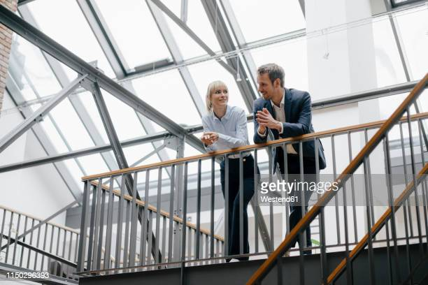 businessman and woman standing in office building, discussing - man made structure stock pictures, royalty-free photos & images