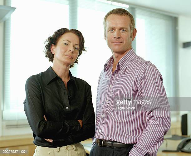 businessman and woman standing in office, portrait - open collar stock photos and pictures