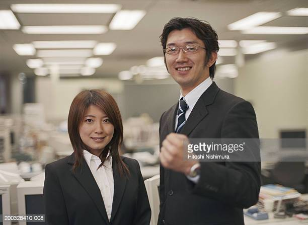 Businessman and woman standing in office, smiling, portrait