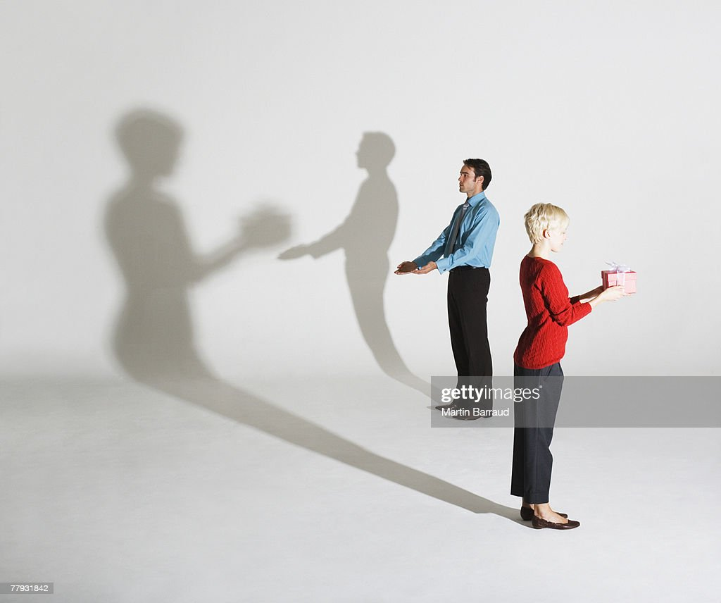 Businessman and woman standing so shadows look like she's giving him a gift : Stock Photo