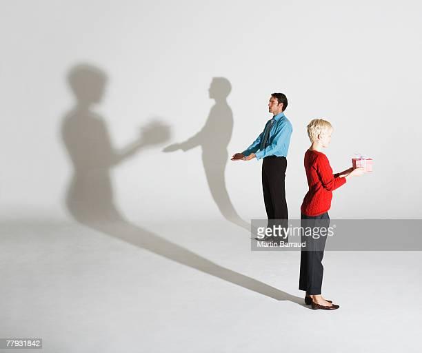 Geschäftsmann und -frau und Schatten, wie sie geben