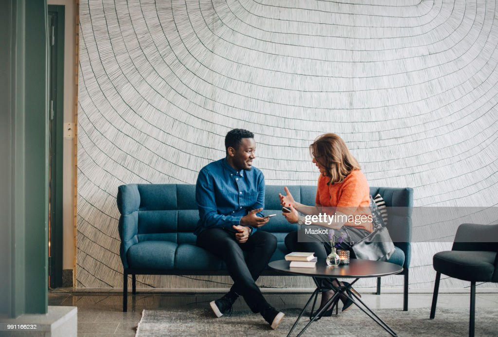 Businessman and woman taking while sitting on couch against wall at conference : Foto de stock