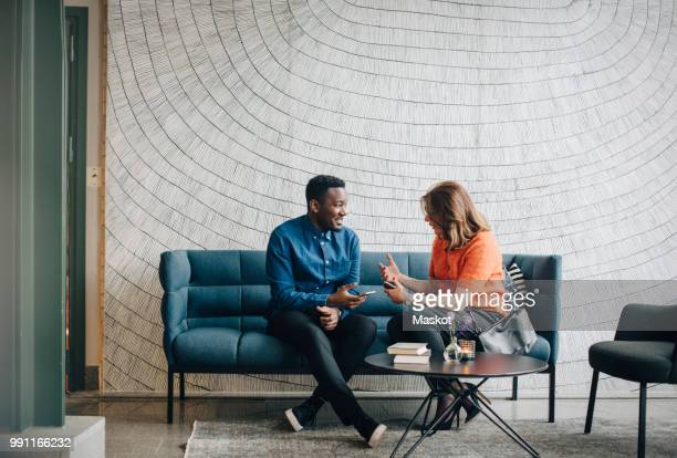 Businessman and woman taking while sitting on couch against wall at conference