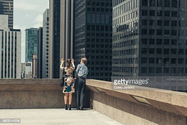 Businessman and woman talking on rooftop corner, Los Angeles, USA