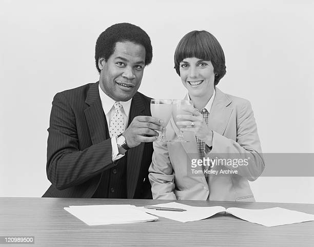 Businessman and woman toasting drink glass, smiling, portrait