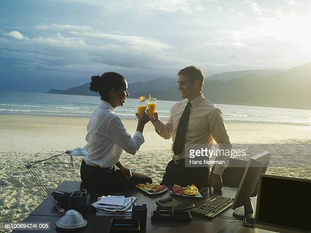 Businessman and woman toasting drinks on beach