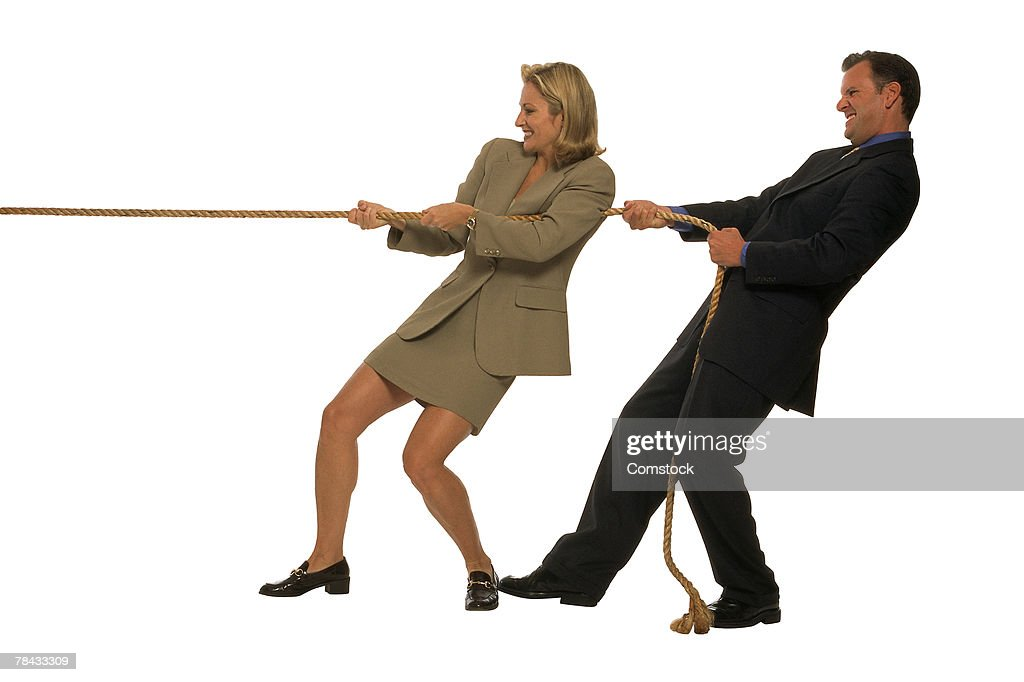 Businessman and woman tugging on rope : Stockfoto