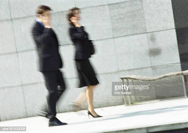 Businessman and woman using cell phone in street, full length, blurred motion