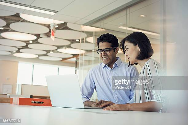businessman and woman using laptop together - truth be told stock photos and pictures