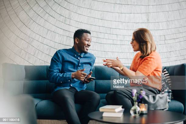 businessman and woman using mobile phones while sitting on couch during conference - talking stock pictures, royalty-free photos & images