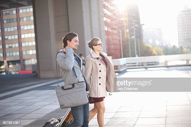 Businessman and woman walking across city rooftop parking lot