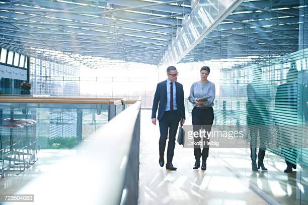 Businessman and woman walking and talking on office balcony
