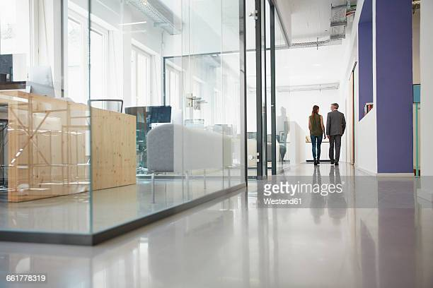 Businessman and woman walking down office corridor