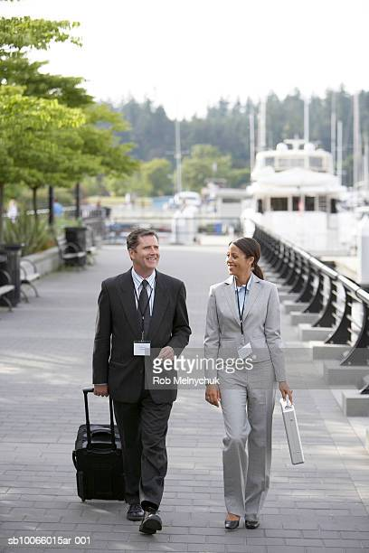businessman and woman walking down seawall and talking - seawall stock pictures, royalty-free photos & images